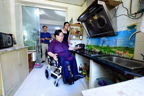 图为在残疾人家中查看无障碍改造情况