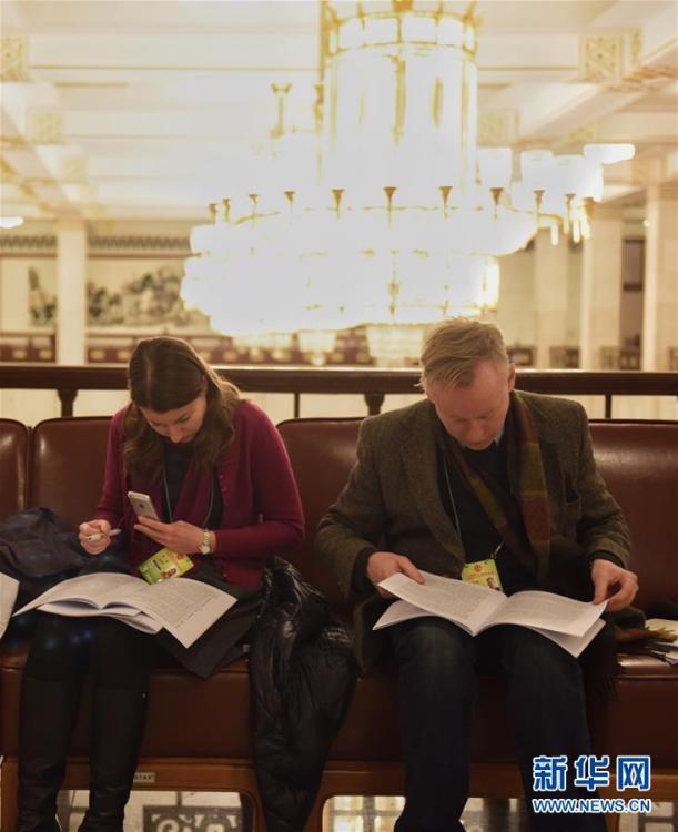 两会记者席地而坐阅读政府工作报告