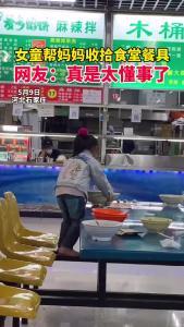 女童帮妈妈收拾食堂餐具