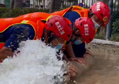 5名消防员用胸膛抵住排水口 让排渍作业顺利进行