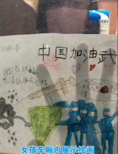 女孩车厢内展示绘画 隔窗为武汉加油!