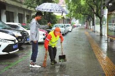 六旬保洁员冒雨清扫,大学生为其撑伞40分钟